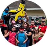 Large group of parents and children dressed up like super heroes